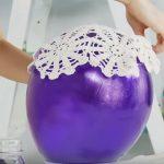 Elle couvre le ballons avec des napperons. Le résultat final est une belle lanterne pour la maison
